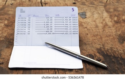 bank account book with silver luxury pen on rustic wood background with copy space