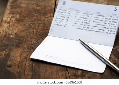 bank account book with silver luxury pen on rustic wood background