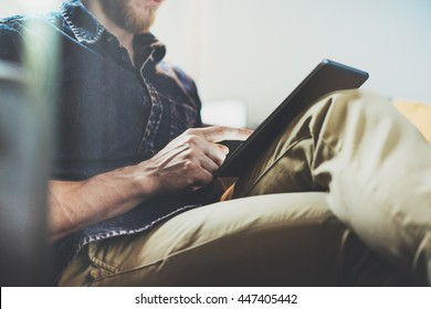Bank account manager reading business news modern Interior Design Loft Office.Man relax Vintage Sofa,Use contemporary tablet,share information.Blurred Background.New Startup Idea Process.Closeup