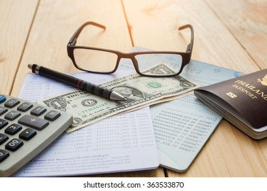 Bank account Pen,dollar,glasses  and calculator with passport