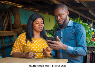 Bank Agent teaching African Market woman how to use a Bank mobile app on his smartphone