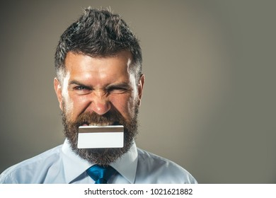 Bank card, creditcard, cash card, business-card - cashless calculation. Crazy boss - emotional ambitious creative cardholder. Attractive manager holds in his teeth credit card.Copy space for advertise