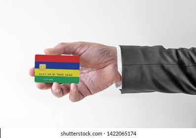 Bank credit plastic card with flag of Mauritius holding man in elegant suit