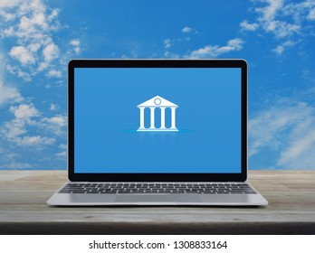 Bank flat icon with modern laptop computer on wooden table over blue sky with white clouds, Business banking online concept
