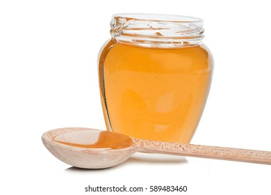 Bank full of yellow liquid honey with a wooden spoon
