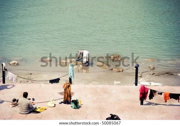 Bank of Ganga river. An old woman washing clothing.
