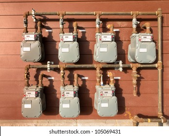Bank of individual residential natural gas meters on building exterior to measure household consumption