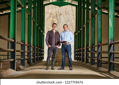 Bank Manager and Farmer posing in barn.