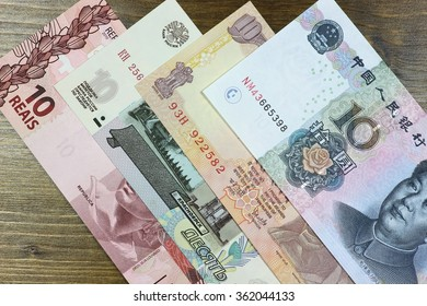 bank notes of the BRIC states on wooden background