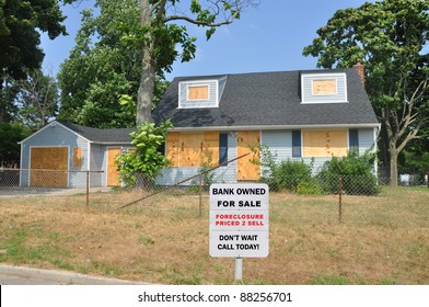 Bank Owned Foreclosure For Sale Sign on Front Yard Lawn of Cape Code Style Suburban Home in Residential Neighborhood