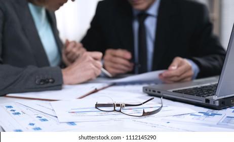 Bank representatives analyzing statistics reports financial charts, paper work