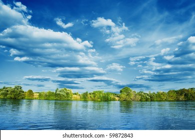 bank of river with green trees on summer day