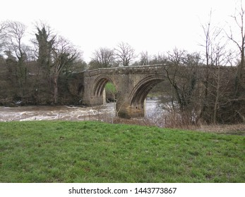the bank of a river showing a stone arched bridge over the water.