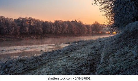 bank of the river with trees covered with rime on a winter morning