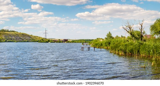 Bank of sunny summer lake with green reed thickets and several wooden piers for fishing and swimming.