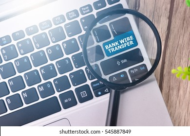 Bank Wire Transfer word written on keyboard view with magnifier glass
