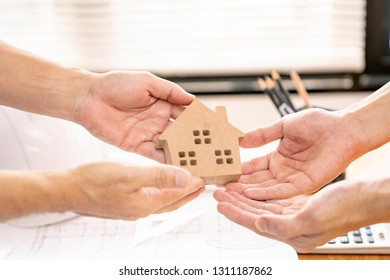 banker or business man handover house to client or customer in office.