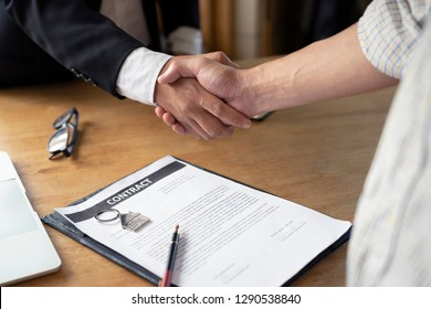 Banker business man shaking hands with client and sign contract document for confirm corporation or finished loan agreement for house or building property.