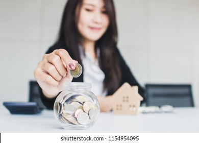 Banker introduces cheap interest for buying residence concept, business woman saving money in glass of jar to get home, housing loan.