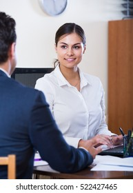 Banking adult agent listening to customer and smiling in agency