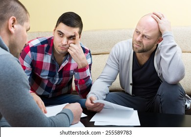 Banking agent explaining adult males how to overcome crisis