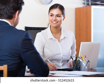Banking european agent listening to customer and smiling in agency