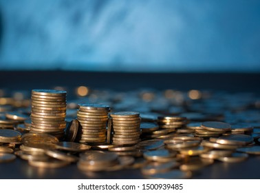 Banking and money trading. Golden metal coins stacked in different combinations on dark blue blurred background. Serbian metal coin, copy space