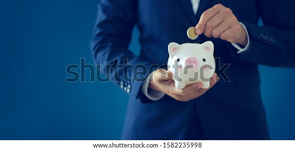 Banking and saving, investment, Businessman holding piggy bank and insert coin on blue background