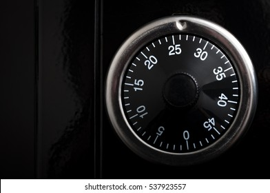 Banking and security concept with copy space and closeup on the dial of a rotary combination lock, an unkeyed mechanism used to secure safes. Turn in a certain combination in order to open the lock