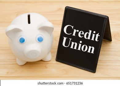 Banking using a credit union, A piggy bank on a desk with chalkboard with text Credit Union