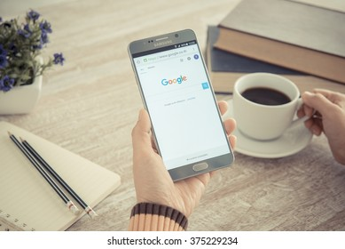 BANKKOK, THAILAND - FEBRUARY 11,2016: Human hands using a smartphone notes 5 show Google search; Vintage Style.