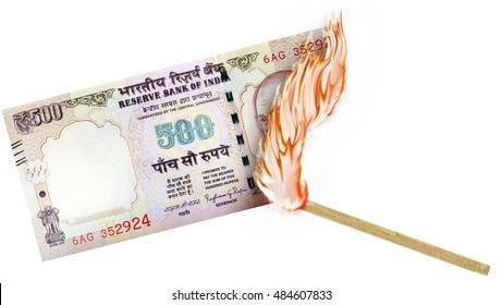 A banknote being burned by a match with burning in a big flame.