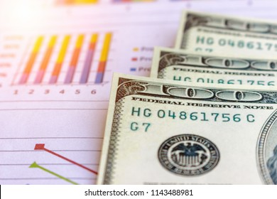 Banknote and coins depicted on economic graphs dollar currency, financial investment concepts that affect the global economy and people's spending, and saving money for future use for indissolubility.