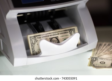 Banknote counter and usd (US dollars) banknotes.