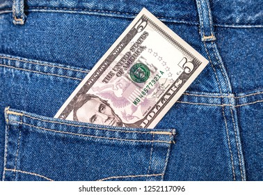 Banknote of five american dollars sticking out of the jeans pocket