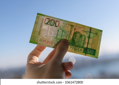 Banknote of new two hundred rubles in hand over city background.