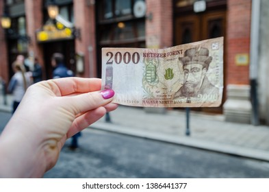 Banknote in two thousand (2000) forints in a female hand against the background of the city.