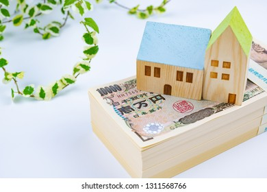 """banknotes of 10000 yen and house model. Translation on bill text: """"Bank of Japan Tickets"""" """"One hundred thousand yen"""" """"The Bank of Japan""""."""