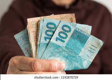 Banknotes of brazilian currency: Reais. Brazil Money. Old retired person paying in cash.