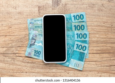 Banknotes of brazilian currency: Reais. Brazil Money. Blank smartphone screen and cash bills on wooden table.