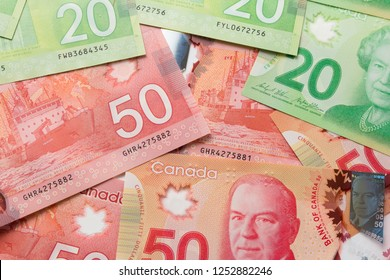 Banknotes of Canadian currency: Dollar. Canada Money. Full frame of bills spread on table and assorted amounts.