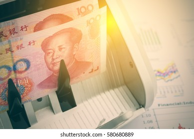 Banknotes of China with a portrait of Mao Zedong on an automatic bill counter. Used for China economy related i.e. industrial PMI, GDP growth, inflation, interest, balance of trade, debt to GDP, etc