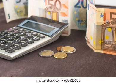 Banknotes and coins with calculator. Euro banknotes on wooden background. Photo for tax, profit and costing. 50 euro, 20 euro, 10 euro. Money and finance