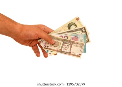 Banknotes from different countries in the hand on white background