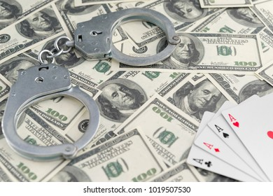 banknotes of dollars, handcuffs, four ace of playing cards. gambling. law violation. ban on gambling