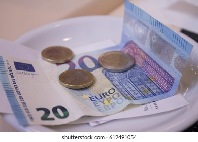 Banknotes and euros on plate