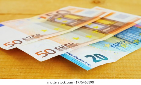 Banknotes fifty and twenty euros on a natural wooden surface close up
