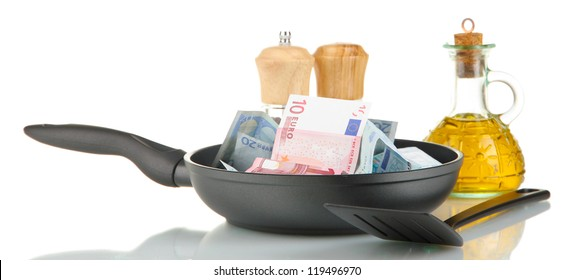 Banknotes in a frying pan with cooking spatula isolated on white