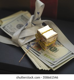 Banknotes as a gift with box wrapped in golden paper on top, concept of success, closeup angled shot