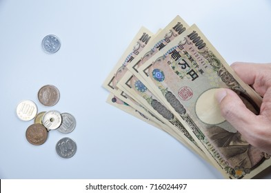 Banknotes of Japanese currency yen background, JPY money with handholding it and many Japanese coins on white background